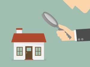 Man holding magnifying glass to home
